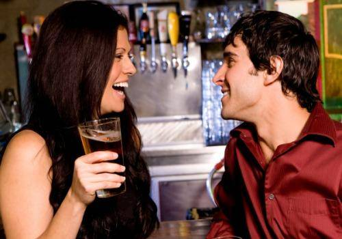 happy man and woman in bar talking
