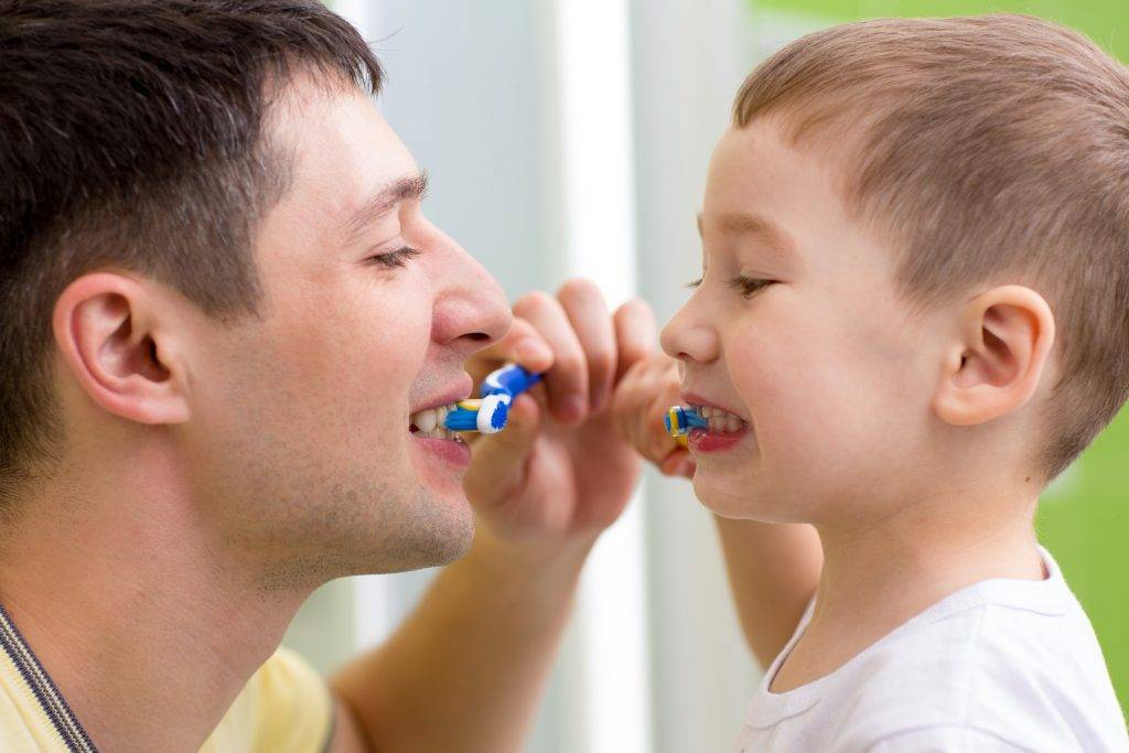 child and his dad brushing teeth in bathroom
