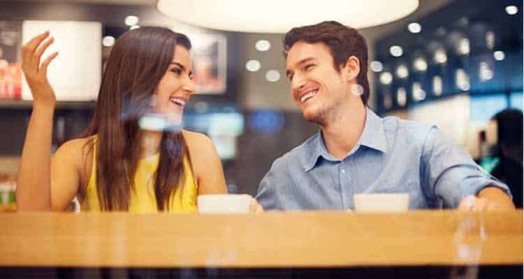 Young couple sitting in cafeteria and drinking coffee