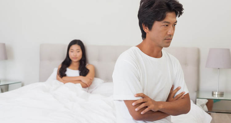 Sad woman sit on bed as husband is gay