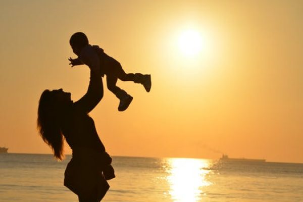 mother and child at beach in sunset