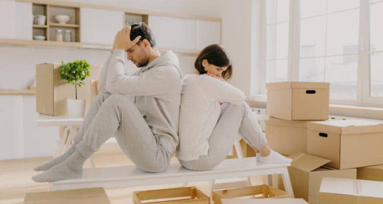 Unhappy young married woman man have leave house move other place sit back each other pose-empty-room-with-stack-boxes-wear-domestic-clothes-socks-have some problem