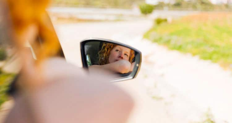 Mirror image of female riding in car