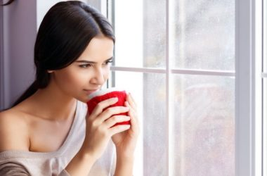 Girl looking out of window having coffee