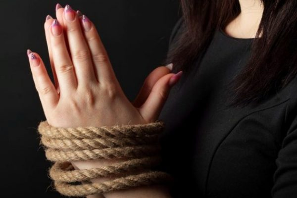 Hands of a woman tied with rope