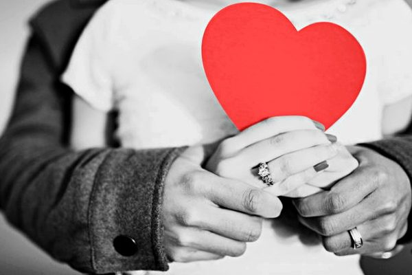 a couple holding a red heart