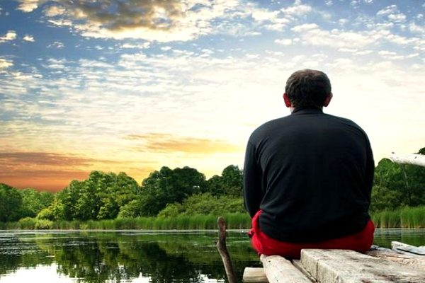 a lonely man sitting by the lake