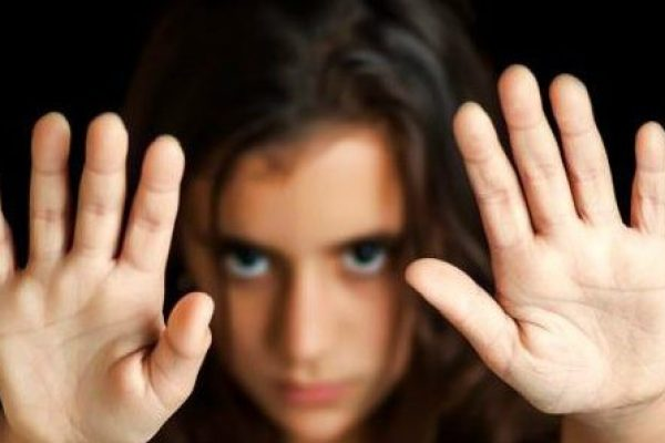 girl with her hand signaling to stop abuse