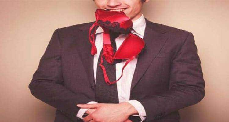 man in office attire with bra in his mouth