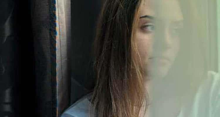 Sad girl looking from window