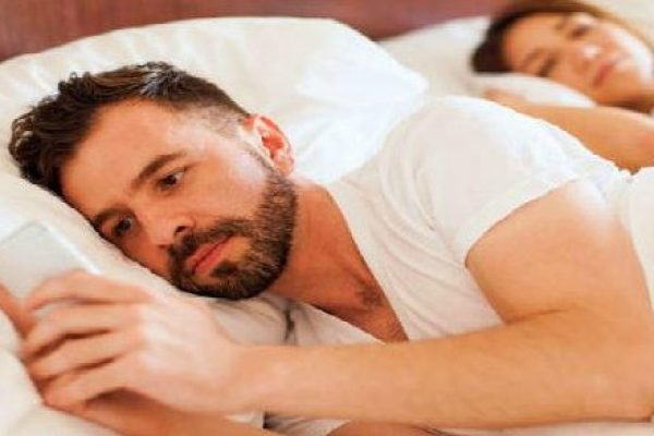 young man texting lover while wife is asleep