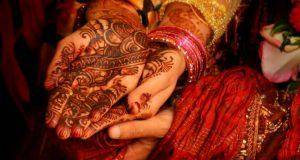 Indian groom holding hands of his bride. Even for a second marriage men tend to be in a better bargaining position