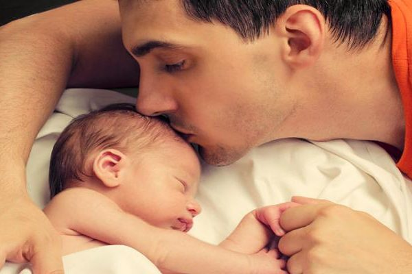 Loving father kissing baby