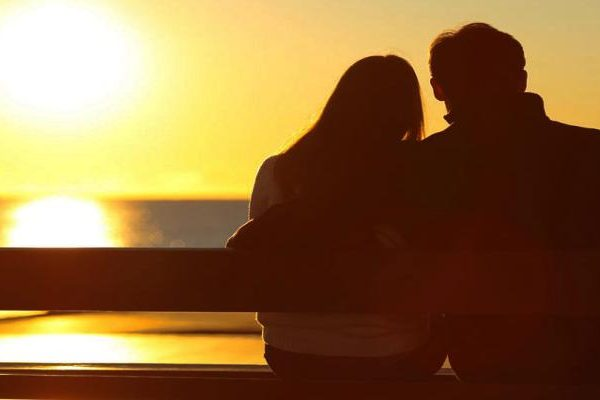 Silhouette of couple watching the sun set