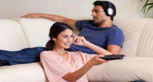 Wife watching tv as husband listens to music