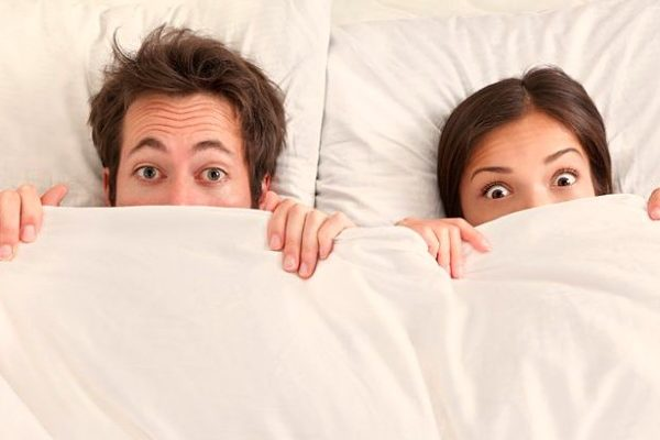 funny wide eyed couple in bed