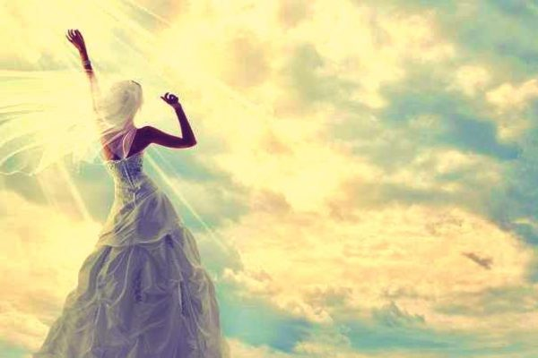 girl in wedding gown looking up at sky