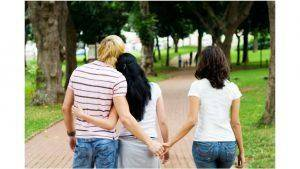 man woman holding hand behind a girls back