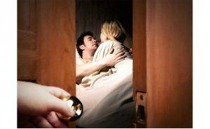 man woman in bed seen thru open door