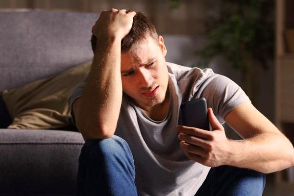 sad man looking at phone