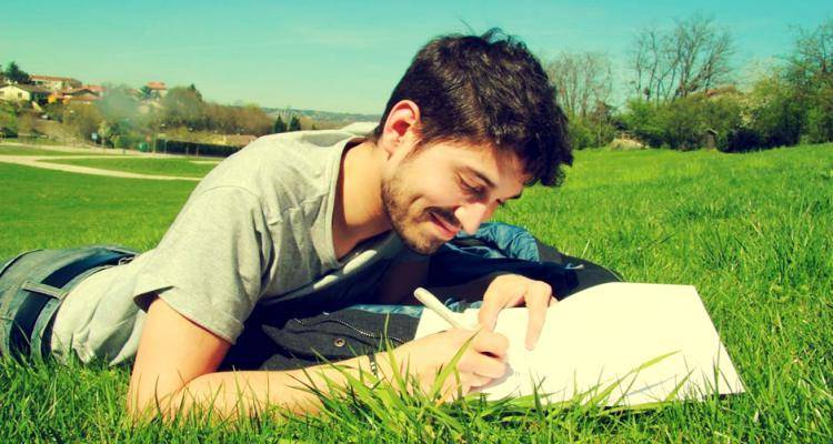 young man on grass, writing on notepad