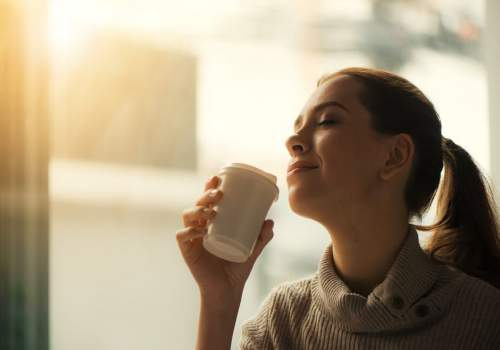 Woman-enjoying-coffee-with-eyes-closed