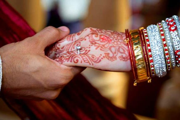 close up of Indian bride and groom hands