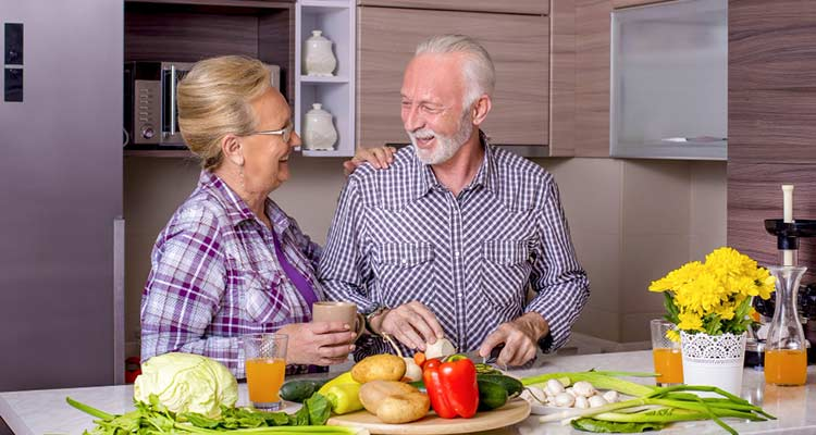 Old couple cooking in a kitchen