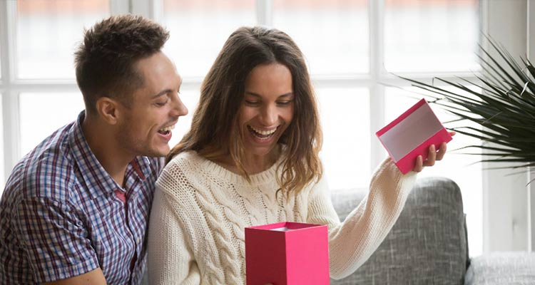 excited young woman opening gift box receiving present from husband