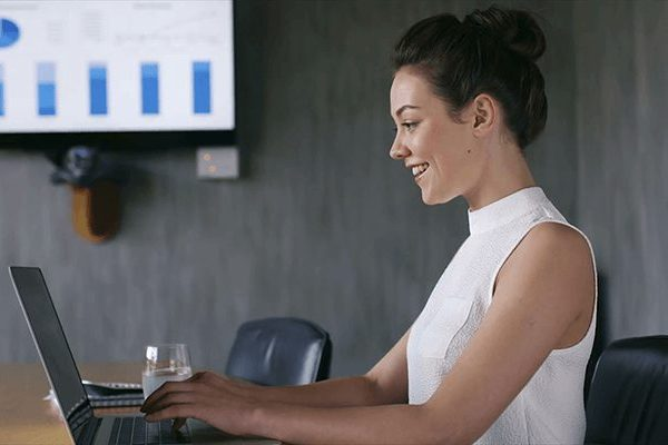 side view of woman looking at laptop