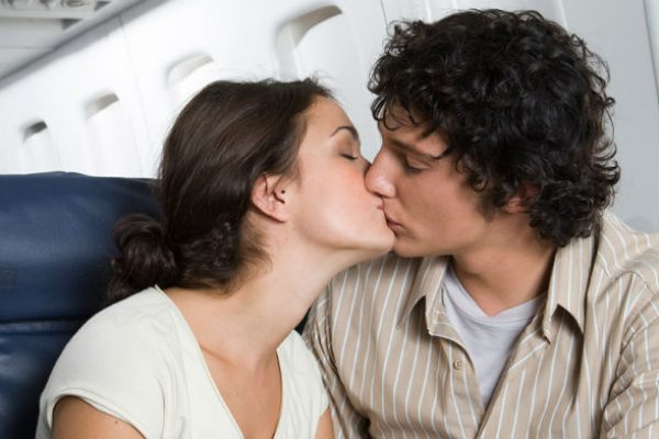 Couple kissing in airplane