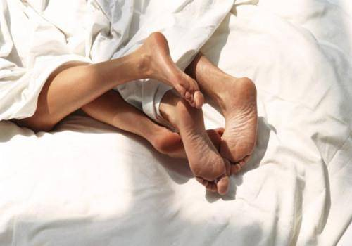 foot of man and woman in bed