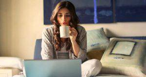 Woman on bed working on laptop