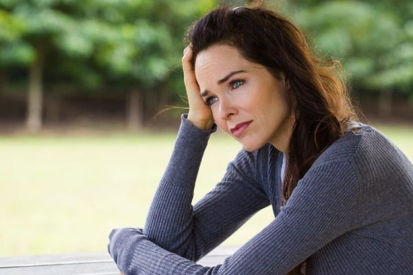close up of a woman, alone, deep in thought