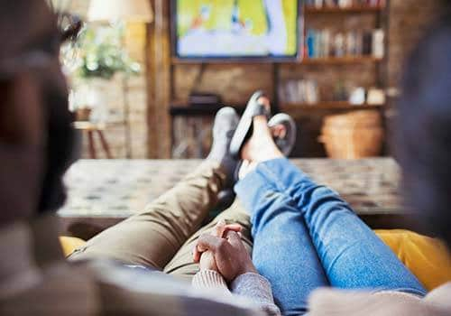 couple laying on sofa and holding hand