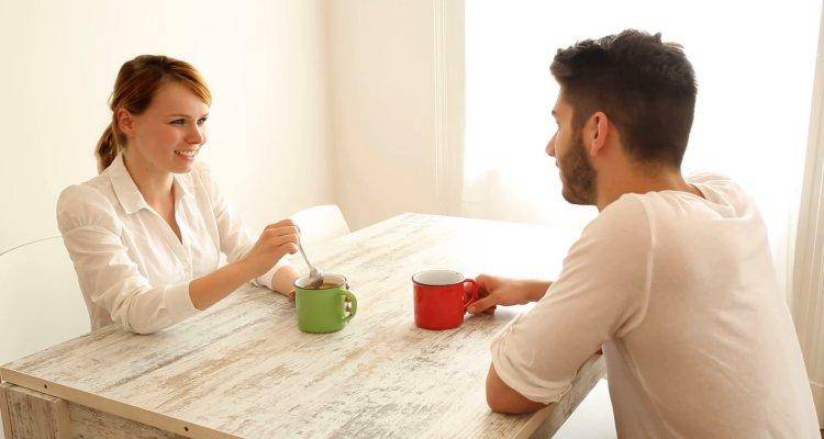 man and woman talking while having coffee