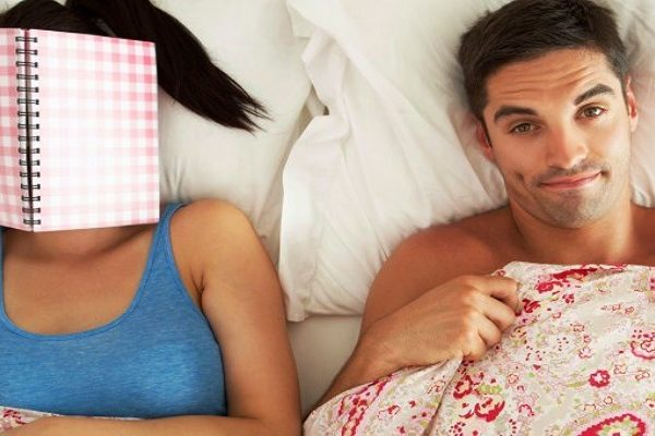 man and woman with book in bed