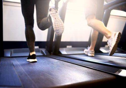 man and woman's foots on a treadmill