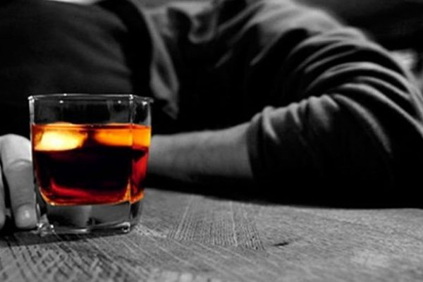 sad man lying on the table with the glass of alcohol
