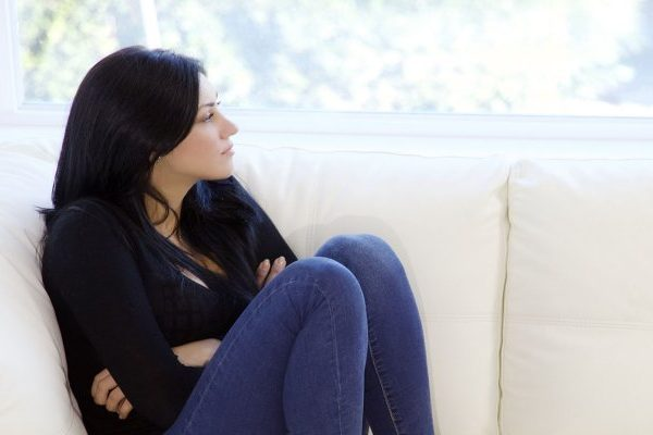 Young-woman-seated-on-sofa-
