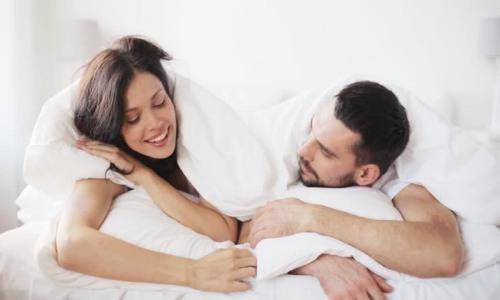 man and woman talking in bed