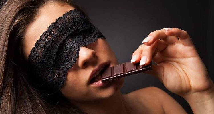 woman having chocolate in mouth