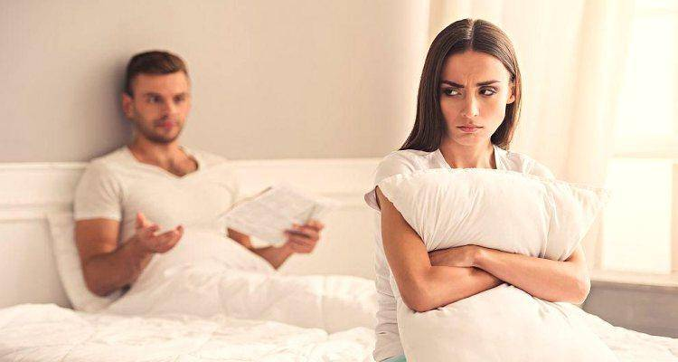 couple not talking to each other sitting on bed