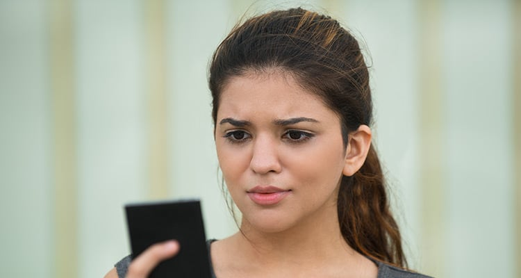 Frowning young woman reading message on cellphone