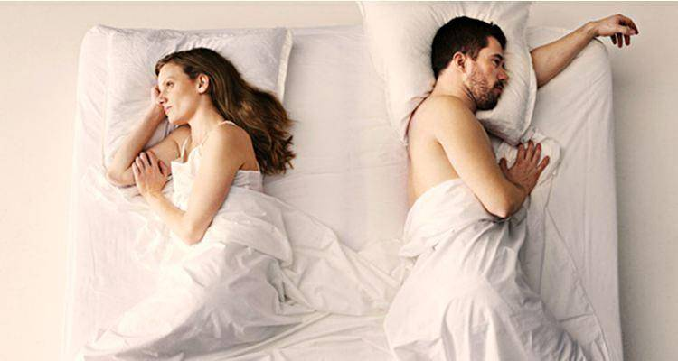 couple not seeing each other in bed