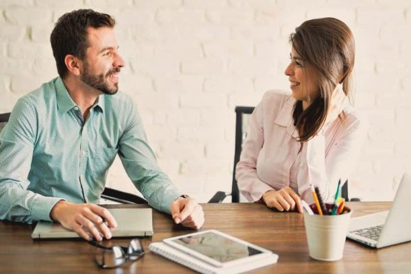 man and woman talking in the office