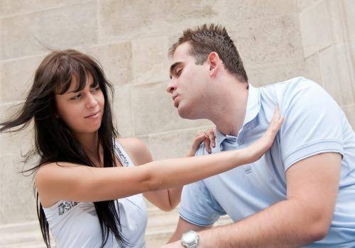 woman trying to stop man from kissing