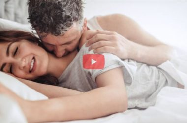 man kissing woman on neck in bed