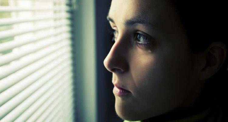sad woman crying seeing outside window