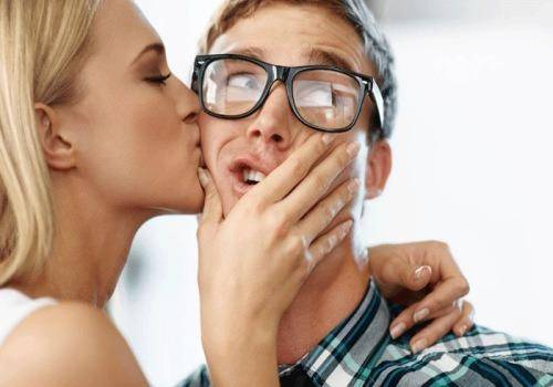 woman kissing amused man
